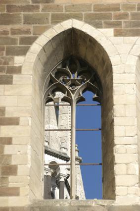 Mal coiffée baie de l'ancienne chapelle, remplages en fleur de lys, vue sur la cathédrale