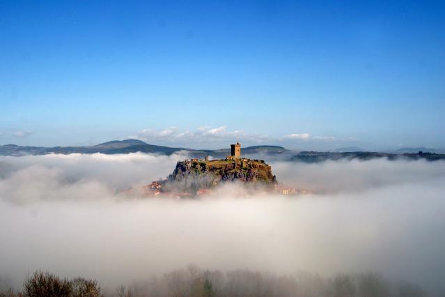 La forteresse de Polignac émergeant au-dessus des nuages